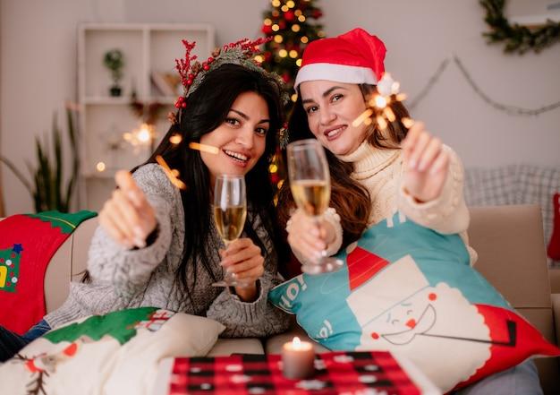 Lächelnde hübsche junge mädchen mit weihnachtsmütze halten gläser champagner und wunderkerzen, die auf sesseln sitzen und die weihnachtszeit zu hause genießen