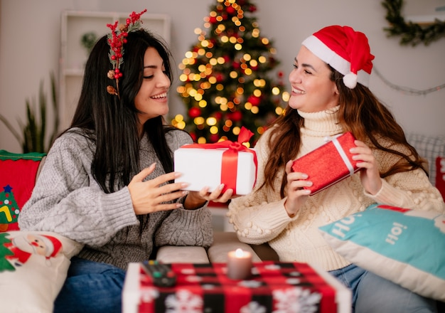 Lächelnde hübsche junge mädchen mit weihnachtsmütze und stechpalmenkranz halten geschenkboxen auf sesseln sitzen und genießen die weihnachtszeit zu hause at
