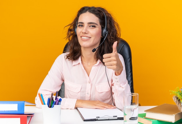 Lächelnde hübsche kaukasische call-center-betreiberin auf kopfhörern, die am schreibtisch sitzen und die bürowerkzeuge hochdrücken
