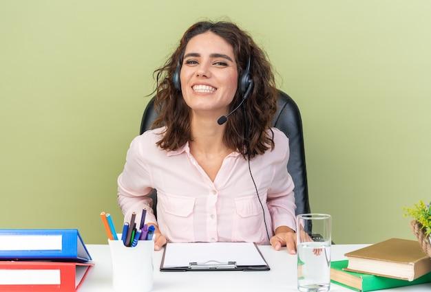 Lächelnde hübsche kaukasische callcenter-betreiberin auf kopfhörern, die am schreibtisch mit bürowerkzeugen sitzen, die auf grüner wand isoliert sind