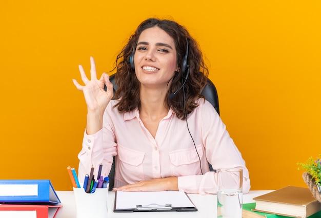 Lächelnde hübsche kaukasische callcenter-betreiberin auf kopfhörern, die am schreibtisch mit bürowerkzeugen sitzen und das ok-zeichen einzeln auf oranger wand gestikulieren