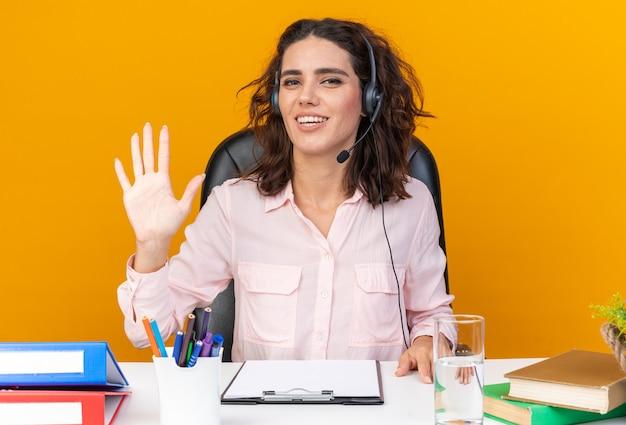 Lächelnde hübsche kaukasische callcenter-betreiberin auf kopfhörern, die am schreibtisch mit bürowerkzeugen sitzen und die hand isoliert auf orangefarbener wand halten?