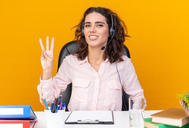 Lächelnde hübsche kaukasische callcenter-betreiberin auf kopfhörern, die am schreibtisch mit bürowerkzeugen sitzen und drei mit den fingern gestikulieren