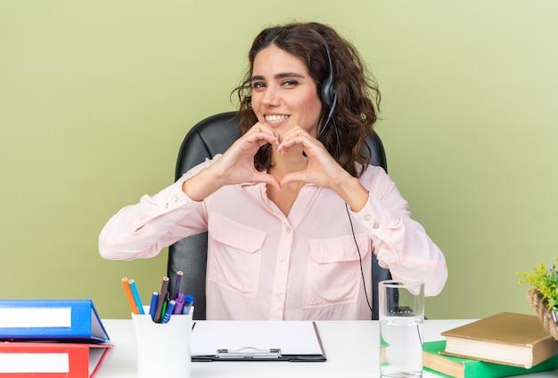 Lächelnde hübsche kaukasische callcenter-betreiberin auf kopfhörern, die am schreibtisch mit bürowerkzeugen sitzen und herzzeichen gestikulieren