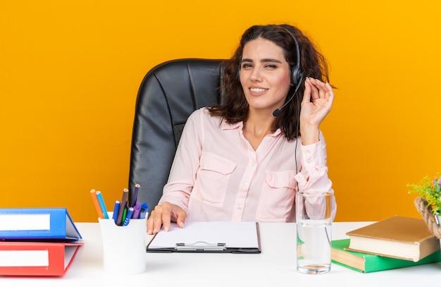 Lächelnde hübsche kaukasische callcenter-betreiberin auf kopfhörern, die mit bürowerkzeugen am schreibtisch sitzen