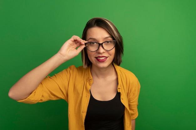 Lächelnde hübsche kaukasische frau betrachtet kamera durch optische brille auf grün