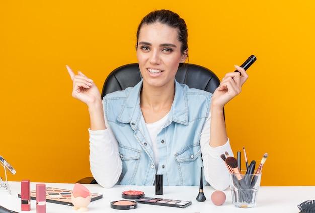 Lächelnde hübsche kaukasische frau, die am tisch mit make-up-tools sitzt und eyeliner hält und auf die seite zeigt