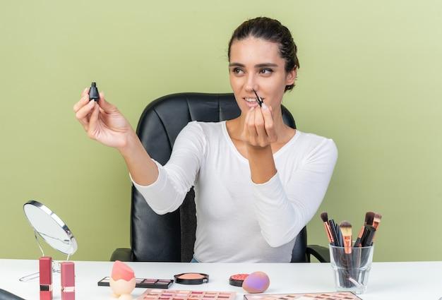 Lächelnde hübsche kaukasische frau, die am tisch mit make-up-tools sitzt und eyeliner hält und betrachtet, isoliert auf olivgrüner wand mit kopierraum