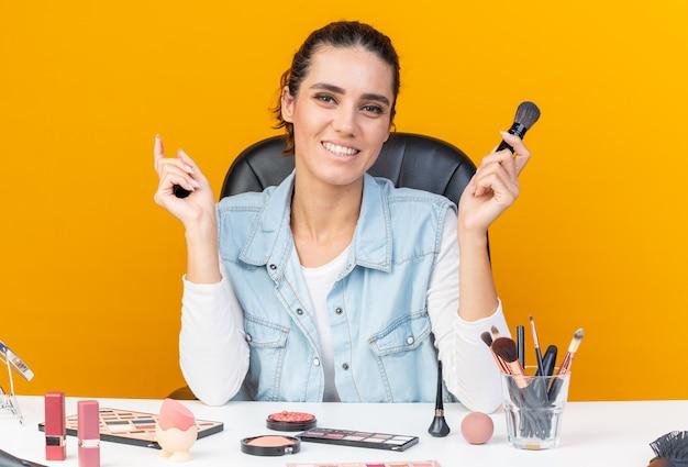 Lächelnde hübsche kaukasische frau, die am tisch mit make-up-tools sitzt und make-up-pinsel und eyeliner hält