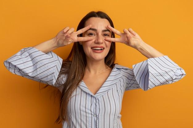 Lächelnde hübsche kaukasische frau gestikuliert siegeshandzeichen mit zwei händen und schaut durch finger isoliert