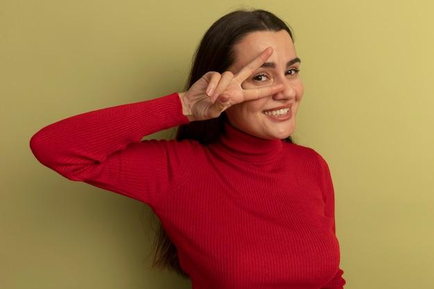 Lächelnde hübsche kaukasische frau gestikuliert siegeshandzeichen und schaut kamera durch finger auf olivgrün