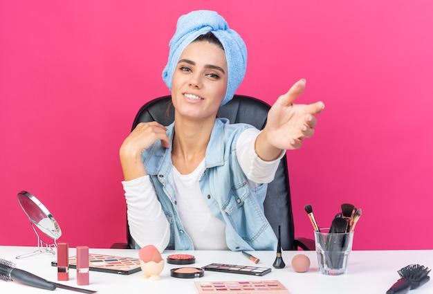 Lächelnde hübsche kaukasische frau mit eingewickeltem haar in handtuch, die am tisch mit make-up-tools sitzt, die ihre hand einzeln auf rosa wand mit kopierraum ausstreckt