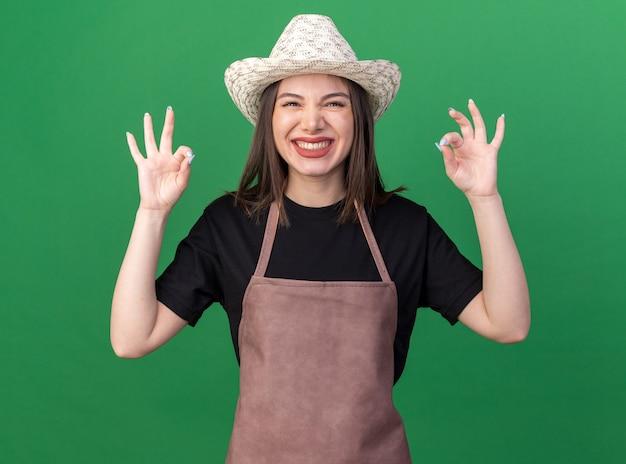 Lächelnde hübsche kaukasische gärtnerin mit gartenhut, die mit zwei händen ein ok-zeichen gestikuliert