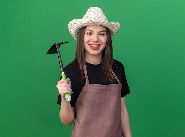Lächelnde hübsche kaukasische gärtnerin mit gartenhut mit hacke-rechen