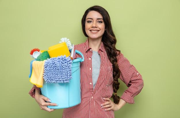 Lächelnde hübsche kaukasische putzfrau, die reinigungsgeräte hält