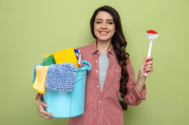 Lächelnde hübsche kaukasische putzfrau, die reinigungsgeräte und bürste hält