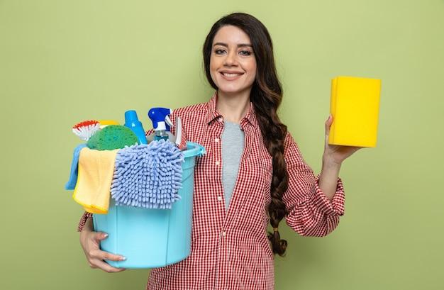 Lächelnde hübsche kaukasische putzfrau, die reinigungsgeräte und schwamm hält