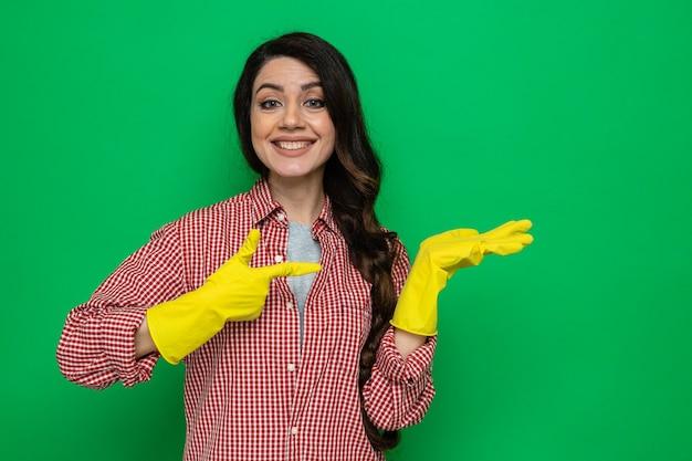 Lächelnde hübsche kaukasische putzfrau mit gummihandschuhen, die auf ihre leere hand zeigt und schaut