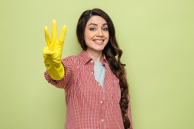 Lächelnde hübsche kaukasische putzfrau mit gummihandschuhen, die drei mit den fingern gestikuliert