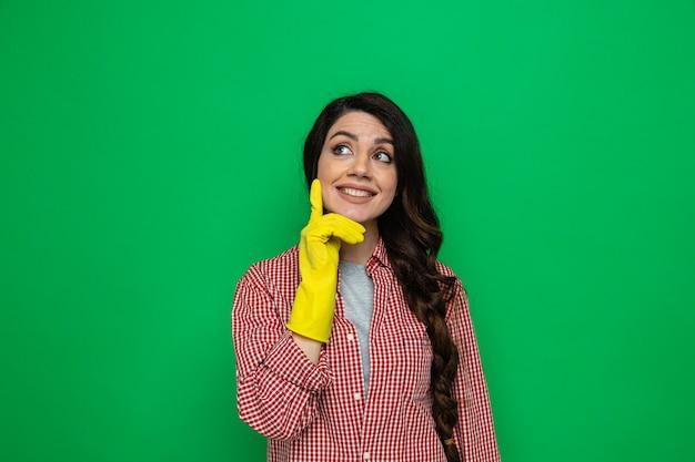Lächelnde hübsche kaukasische putzfrau mit gummihandschuhen, die sich die hand aufs gesicht legt und zur seite schaut