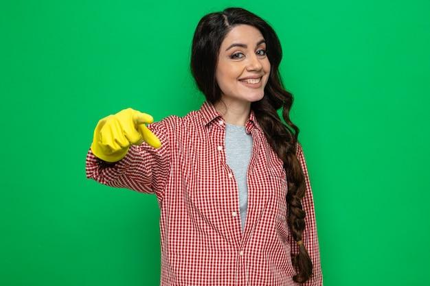 Lächelnde hübsche kaukasische putzfrau mit gummihandschuhen, die zeigen und schauen