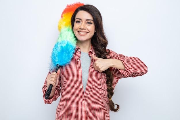 Lächelnde hübsche kaukasische putzfrau mit staubwedel und daumen hoch