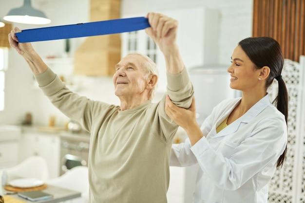 Lächelnde hübsche krankenschwester, die einem älteren mann hilft, zu hause übungen zu machen