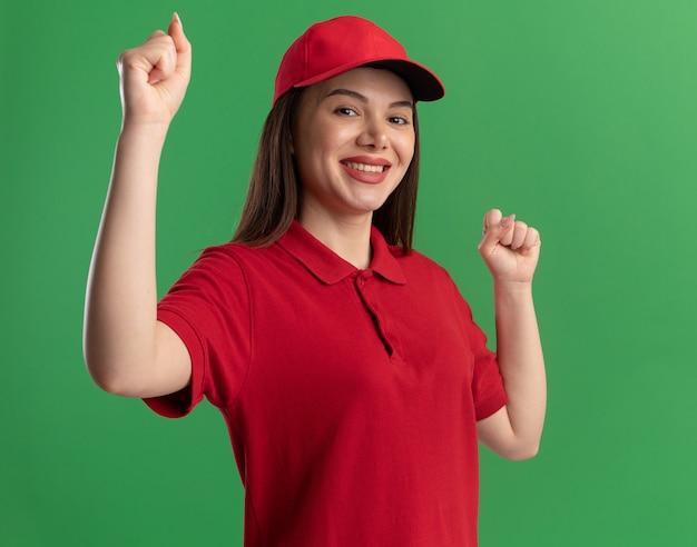Lächelnde hübsche lieferfrau in uniform hält fäuste