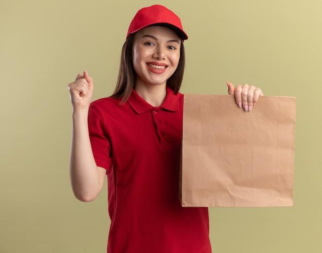 Lächelnde hübsche lieferfrau in uniform hält faust und hält papierpaket auf olivgrün