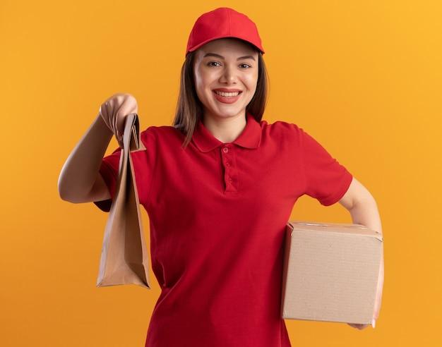 Lächelnde hübsche lieferfrau in uniform hält papierpaket und karton auf orange