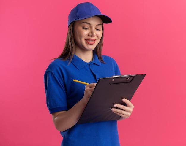 Lächelnde hübsche lieferfrau in uniform schreibt mit bleistift in die zwischenablage