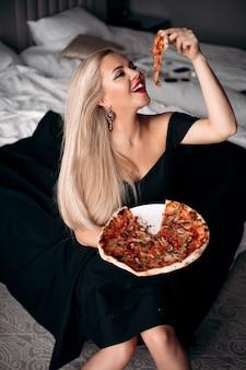 Lächelnde hübsche modische frau im schwarzen kleid, die ein stück pizza hält, während sie auf dem bett in ihrer wohnung sitzt
