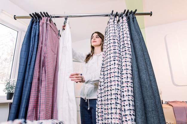 Lächelnde hübsche weibliche modedesignerin, die nahe wäscheständer mit handgemachten hosen steht, während sie im modestudio arbeitet. schönes professionelles designerfrauenarbeitskonzept des lebensstils.