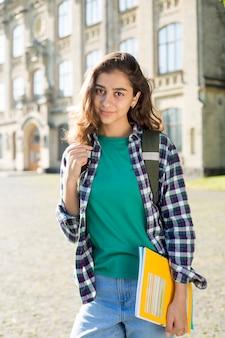 Lächelnde indische junge studentin hält die pädagogische buchstellung. glückliches brunettemädchen nahe der universität.