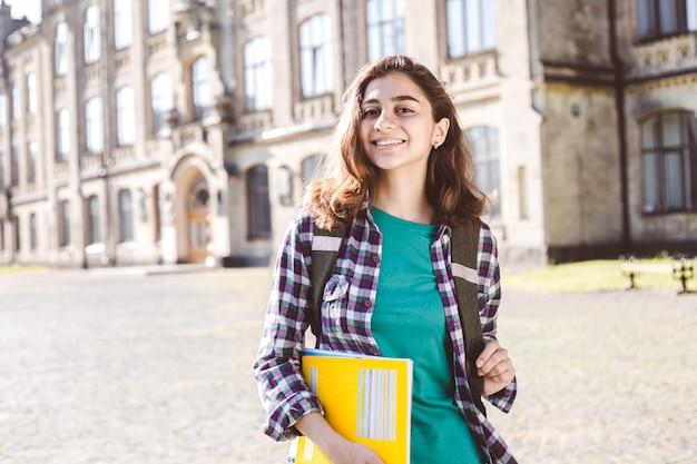 Lächelnde indische junge studentin hält pädagogische bücher
