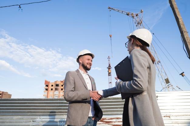 Lächelnde ingenieure, die hände an der baustelle für architekturprojekt rütteln