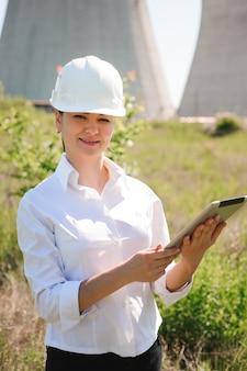 Lächelnde ingenieurfrau mit tablette auf elektrotankstelle.