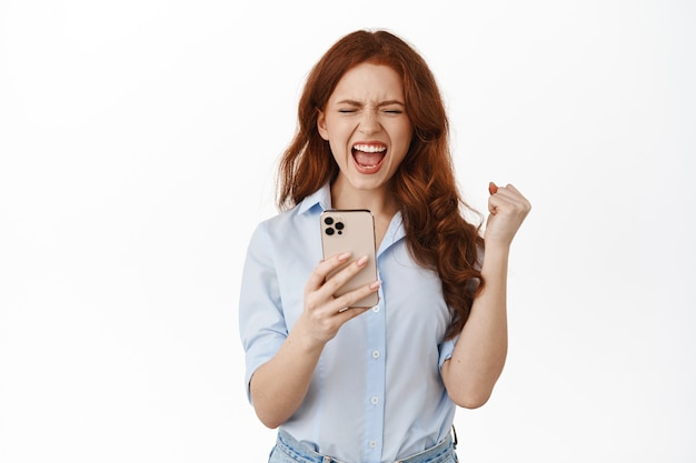Lächelnde ingwerfrau, die smartphone auf weiß hält