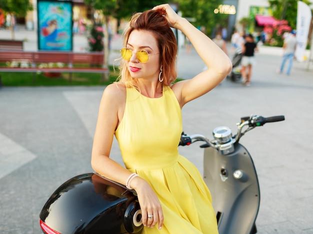Lächelnde ingwerfrau im gelben kleid, das mit dem motorrad reitet, reist und spaß hat. trage ein stylisches sommeroutfit.
