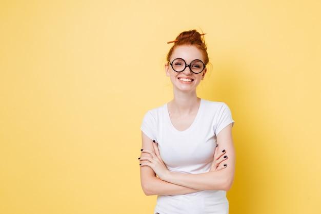 Lächelnde ingwerfrau in den brillen, die mit verschränkten armen aufwerfen