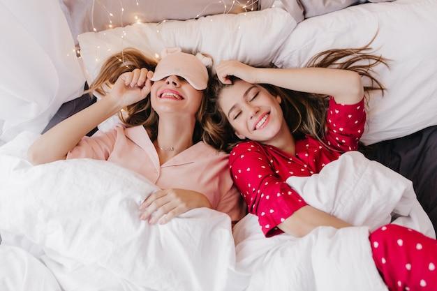 Lächelnde inspirierte frau im roten schlafanzug, der im bett schläft. überkopfporträt der lachenden schwestern, die am frühen morgen unter der decke posieren.