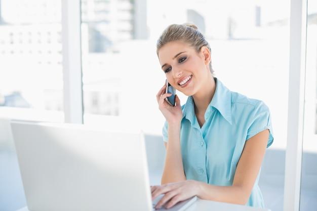 Lächelnde intelligente geschäftsfrau am telefon bei der anwendung des laptops