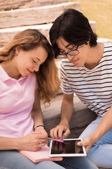 Lächelnde jugendliche, die internet auf tablette auf treppe surfen