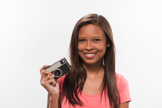 Lächelnde jugendliche, die kamera auf weißem hintergrund hält