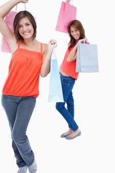 Lächelnde jugendliche gefolgt von einem freund und beide halten kauftaschen
