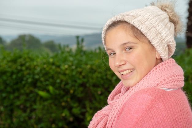 Lächelnde jugendliche mit rosa strickjacke und winterhut