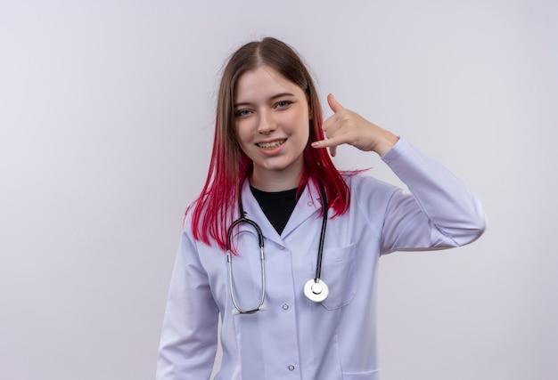 Lächelnde junge ärztin, die das medizinische gewand des stethoskops trägt, das telefonanrufgeste auf lokalisiertem weißem hintergrund zeigt