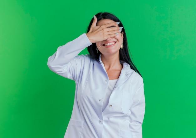 Lächelnde junge ärztin, die medizinische robe trägt, die augen mit hand lokalisiert auf grüner wand mit kopienraum bedeckt