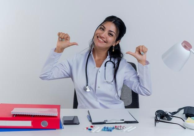 Lächelnde junge ärztin, die medizinische robe und stethoskop trägt, sitzt am schreibtisch mit medizinischen werkzeugen, die auf sich selbst zeigen, isoliert