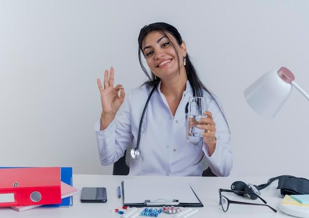 Lächelnde junge ärztin, die medizinische robe und stethoskop trägt, sitzt am schreibtisch mit medizinischen werkzeugen, die halten glas des wassers tun ok zeichen lokalisiert